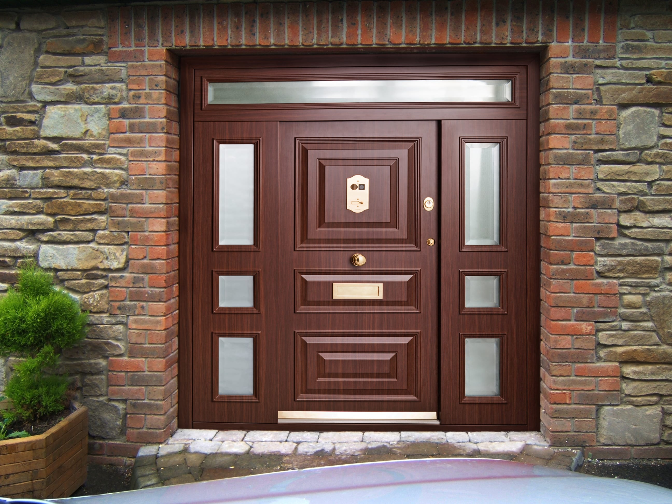 traditional custom security door with wood paneling and glass sidelight windows